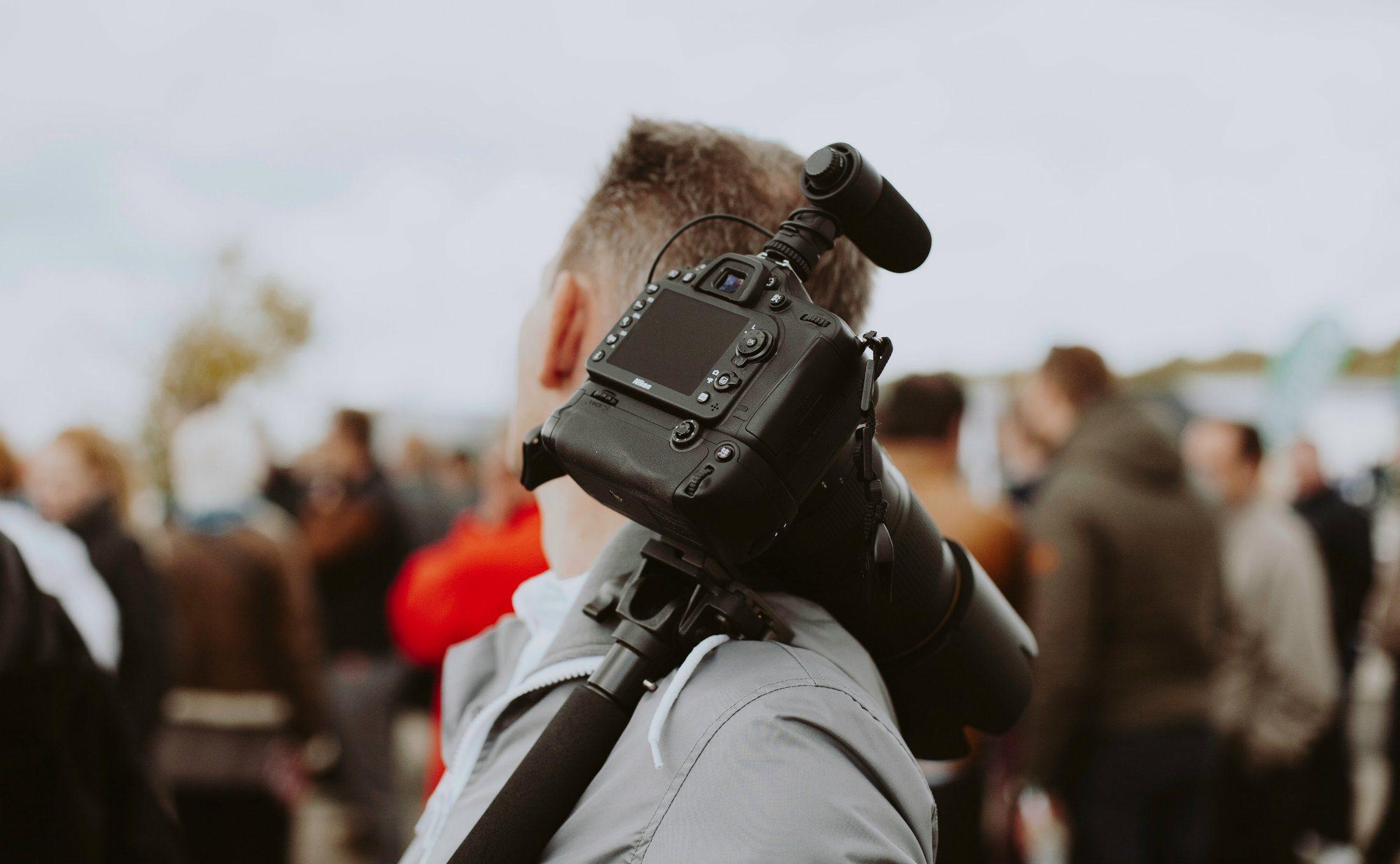 Junger Mann mit Kamera über der Schulter